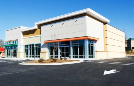 Commercial office building exterior painted tan, white, black, and orange